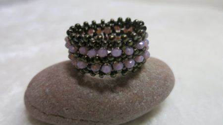 image of beaded ring in bronze lila-on stone
