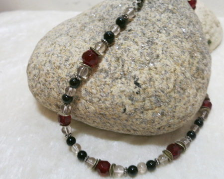 necklace with red and black beads on stone
