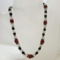 necklace with red and black beads on clear bust
