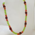 necklace with green red glass beads on bust