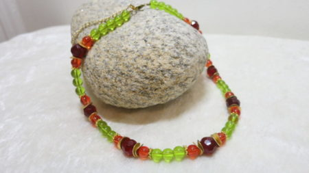necklace with green red glass beads laying in stone