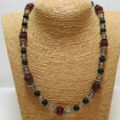 necklace with red and black beads on bust