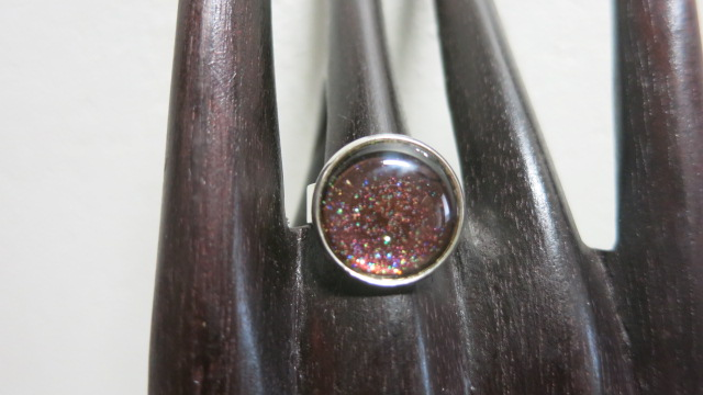 ring with red glitter on wooden display