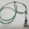 Long necklace green with cone tassel laying