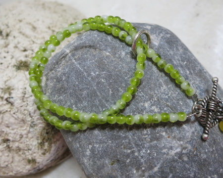 bracelet green color with pendant at toggle on stone