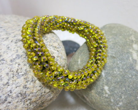 bracelet rolled in golden yellow laying on stones