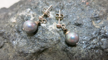 ear studs with hanging shell beads in grey on stone