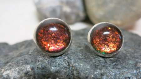 ear studs glittering in red and aubergine front in detail