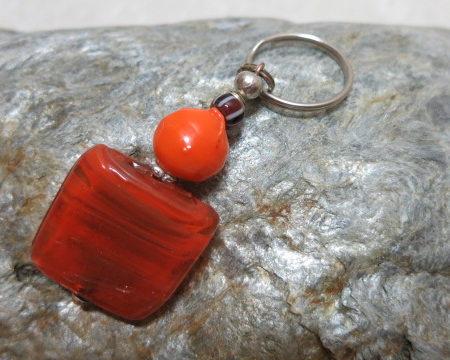 keyringpendant square orange red laying on stone