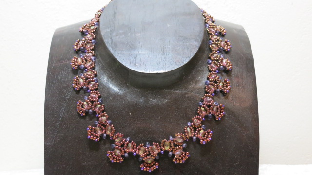 necklace collier coper elegant ethnostyle laying on wooden bust