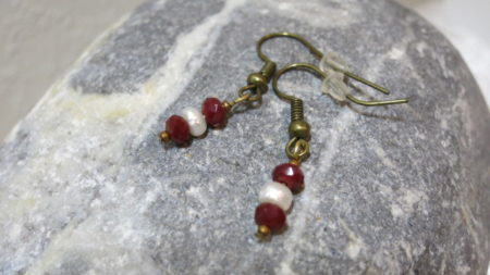 earring small with one freshwater pearl and red faceted beads laying