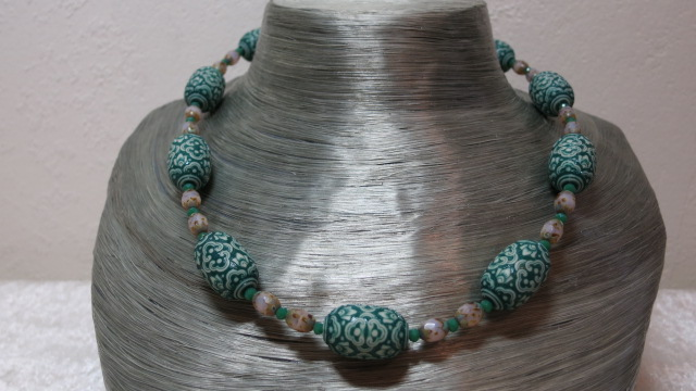 necklace patterned bead greencolored with faceted beads between on silvery bust