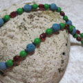 necklace with turquoise lava and green and red beads laying on shell