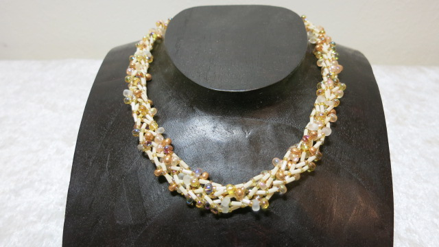 braided necklace opaque gold black frosted white on wooden bust