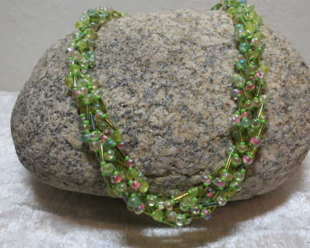 braided necklace green pink colored laying on stone