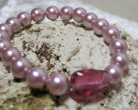 bracelet rosy glass beads on elasitc laying on shell