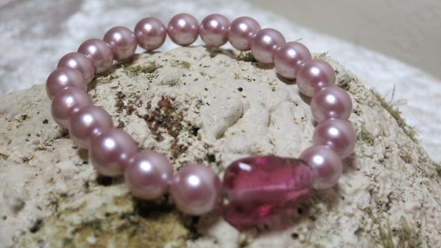 bracelet rosy glass beads on elasitc laying on shell