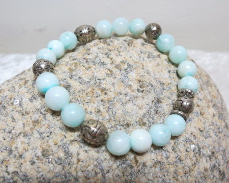 bracelet mint colored silvery beads on elastic laying on shell