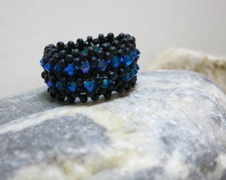 ring beaded black glittering blue on grey stone