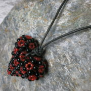 pendant heart black red colors threaded with leather tape view from above