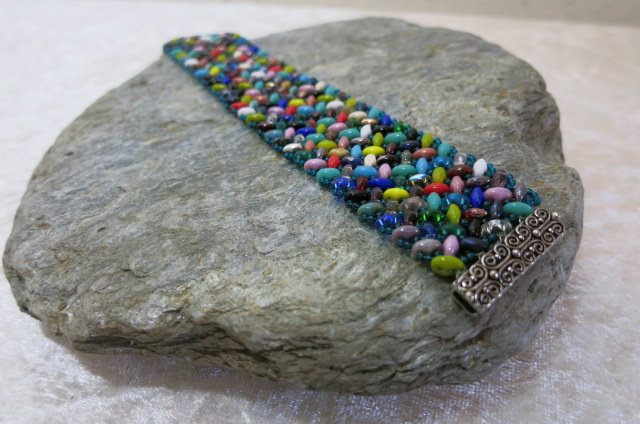 bracelet colorful with decorated closure laying on stone